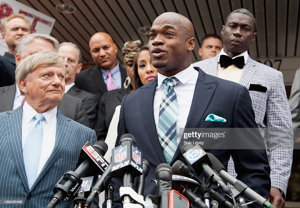Defense attorney Rusty Hardin and NFL running back Adrian Peterson of the of the Minnesota Vikings address the media after Peterson plead 'no...