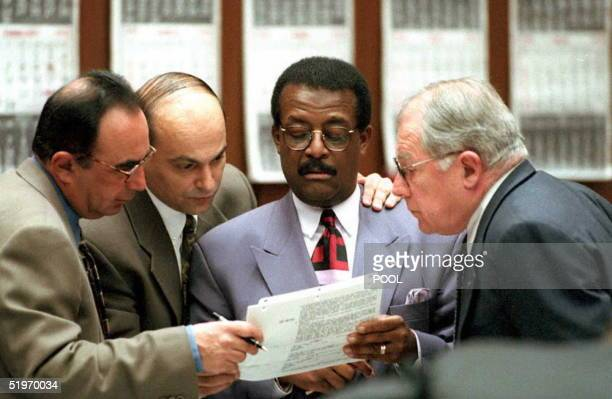 Defense attorneys in the OJ Simpson murder case Robert Sahpiro Johnnie Cochran Jr FLee Bailey and investigator Bill Pavelic review a document during...