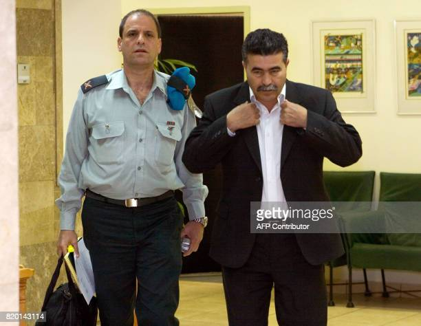 Defense Minister Amir Peretz adjusts his jacket as he and an unidentified military aide walk through the the Prime Ministry building in Jerusalem to...