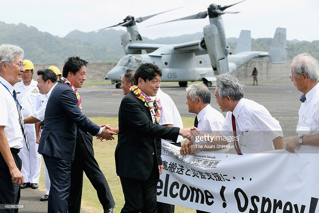 Defense Minister Itsunori Onodera (C) is welcomed by Ogasawara village officials upon his arrival by an Osprey aircraft to Chichijima Island on July 28, 2014 in Ogasawara, Tokyo, Japan. The defense minister unveiled a plan that would use the Self-Defense Forces Osprey aircraft for airlifting sick or injured people in need of immediate medical attention from the Ogasawara islands to hospitals on the mainland.