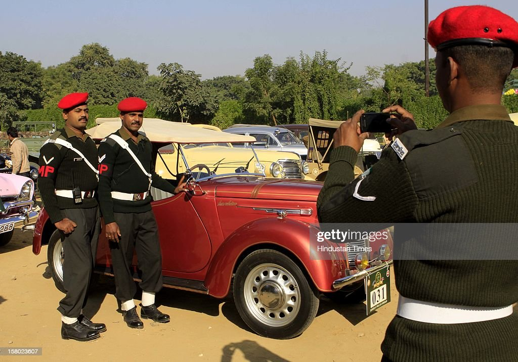 Defense personnel clicked themselves with a vintage car during the '21 Gun Salute Vintage Rally' on December 9, 2012 in New Delhi, India.