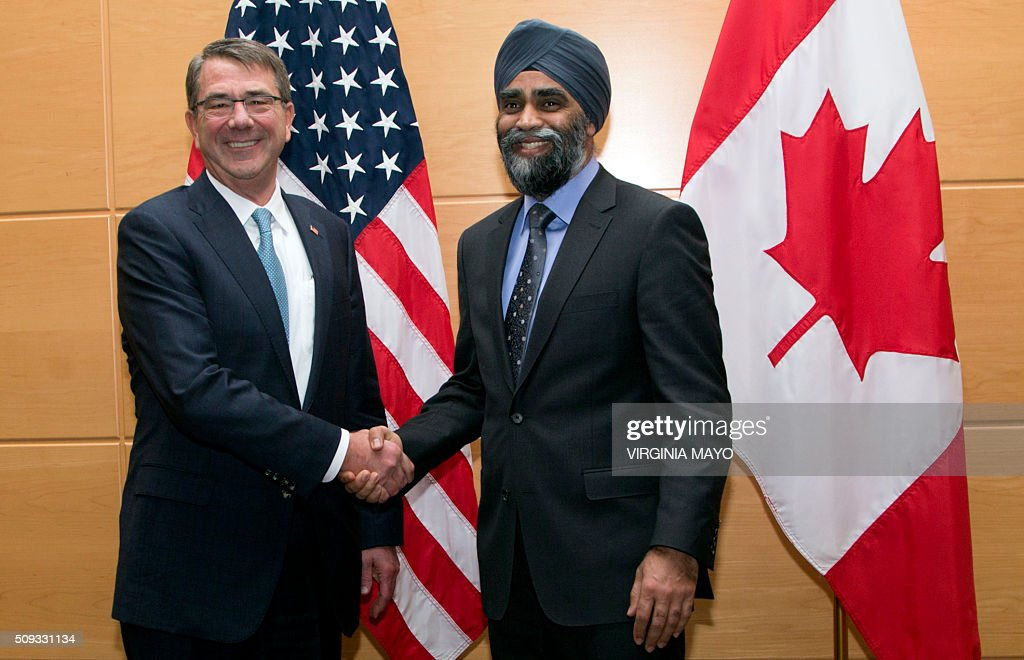 US Defense Secretary Ashton Carter (L) shakes hands with Canadian Defense Minister Harjit Singh Sajjan prior to a bilateral meeting at NATO headquarters in Brussels on February 10, 2016. NATO defense ministers convene a two-day meeting to discuss current defence issues and whether the Alliance should take a more direct role in dealing with its gravest migrant crisis since WWII. / AFP / POOL / Virginia Mayo