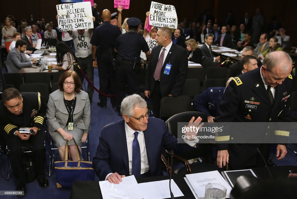 S Defense Secretary Chuck Hagel and Chairman of the Joint Chiefs of Staff Army Gen Martin Dempsey find their seats as demonstrators protest against...