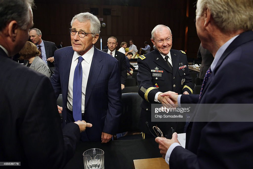 U.S. Defense Secretary Chuck Hagel (2nd L) and Chairman of the Joint Chiefs of Staff Army Gen. Martin Dempsey (3rd L) talk with Senate Armed Services Committee members Sen. Tim Kaine (D-VA) and Sen. Angus King (I-ME) after a hearing in the Hart Senate Office Building on Capitol Hill September 16, 2014 in Washington, DC. Senators questioned the top military and civilian leaders about the threat posed by the terrorist group calling itself the Islamic State of Iraq and the Levant or ISIL.