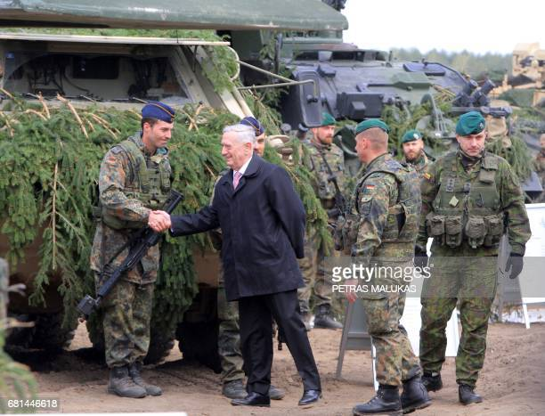 US Defense Secretary James Mattis shakes hands with a German soldier as he meets with US troops deployed in Lithuania with representatives of the...
