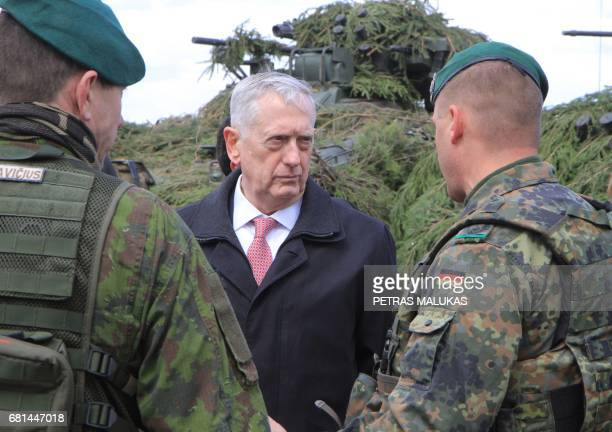 US Defense Secretary James Mattis talks with a German and a Lithuanian soldier as he meets with US troops deployed in Lithuania with representatives...