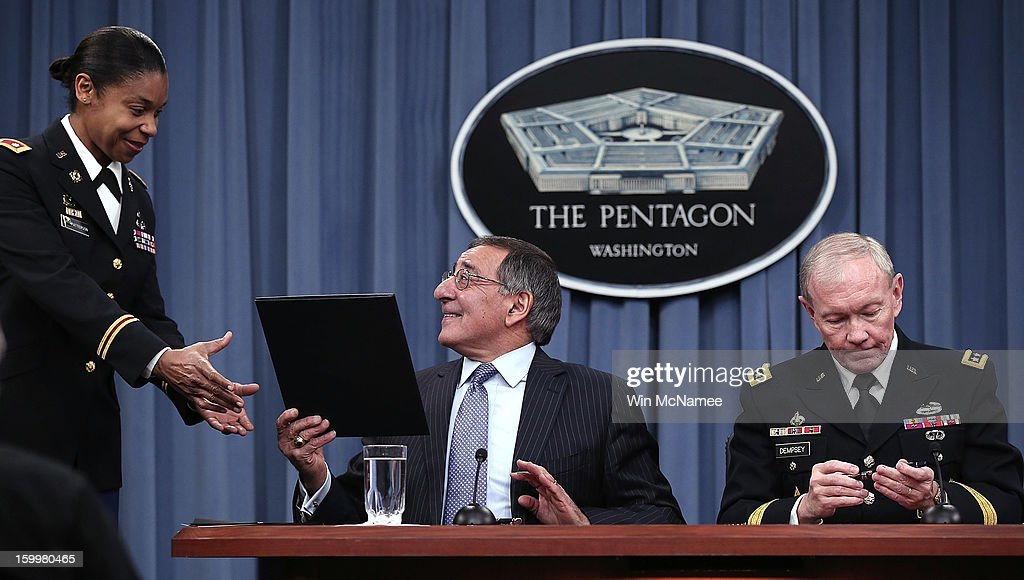 U.S. Defense Secretary Leon Panetta (C) hands recently signed orders to an aide that will remove a ban on women in combat positions with Chairman of the Joint Chiefs of Staff General <a gi-track='captionPersonalityLinkClicked' href=/galleries/search?phrase=Martin+Dempsey&family=editorial&specificpeople=2116621 ng-click='$event.stopPropagation()'>Martin Dempsey</a> (R) at the Pentagon January 24, 2013 in Arlington, Virginia. The U.S. Army and the Marine Corps will present plans to open most combat occupations to women by May 15.