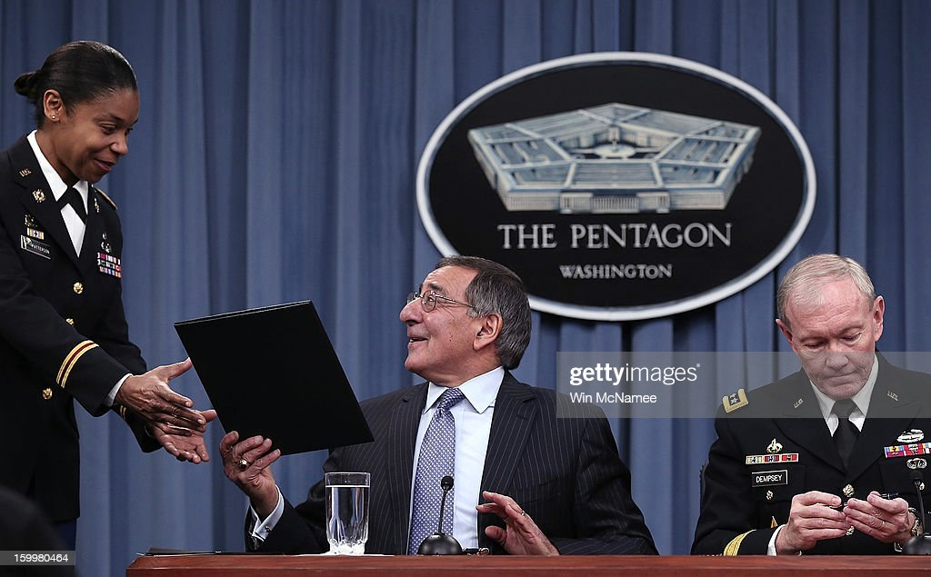 U.S. Defense Secretary Leon Panetta (C) hands recently-signed orders to an aide that will remove a ban on women in combat positions with Chairman of the Joint Chiefs of Staff General Martin Dempsey (R) at the Pentagon January 24, 2013 in Arlington, Virginia. The U.S. Army and the Marine Corps will present plans to open most combat occupations to women by May 15.