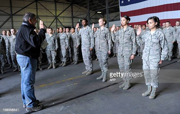 US Defense Secretary Leon Panetta performs a swearingin ceremony to reenlist four troops during his visit to Incirlik Air Base Turkey on December 14...
