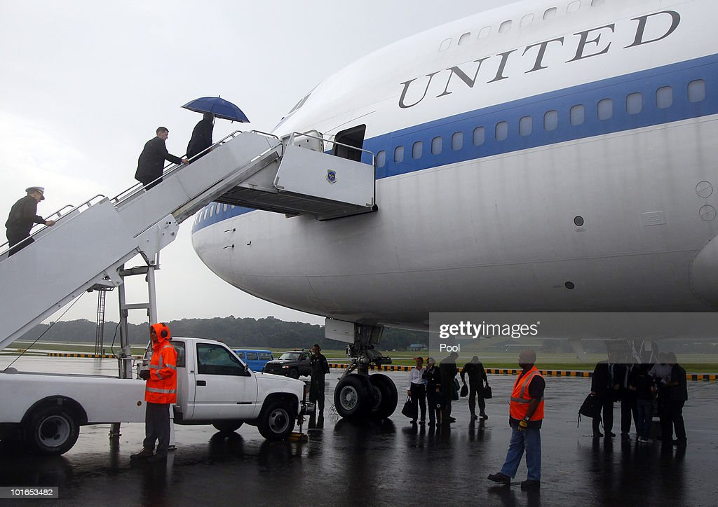 U.S. Defense Secretary Robert M. Gates holds an umbrella as he boards a U.S. Military aircraft at Paya Labar Airfield on June 6, 2010 in Singapore. The 9th IISS Asia Security Summit will ran from June 4 to 6, 2010.