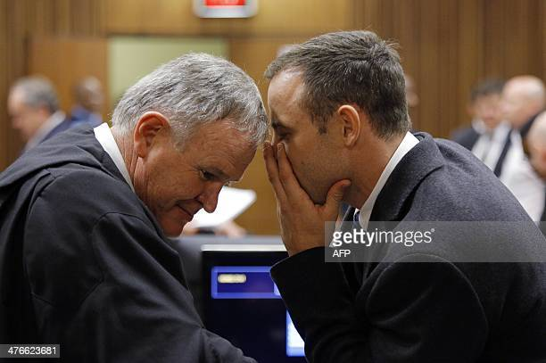 Defense team leader Barry Roux talks to South African Paralympic athlete Oscar Pistorius on the second day of his trial at the North Gauteng High...