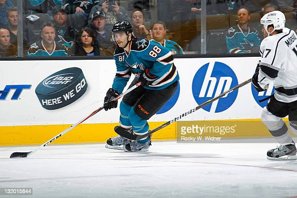 Defenseman Brent Burns of the San Jose Sharks skates with the puck against left wing Ethan Moreau of the Los Angeles Kings at the HP Pavilion on...