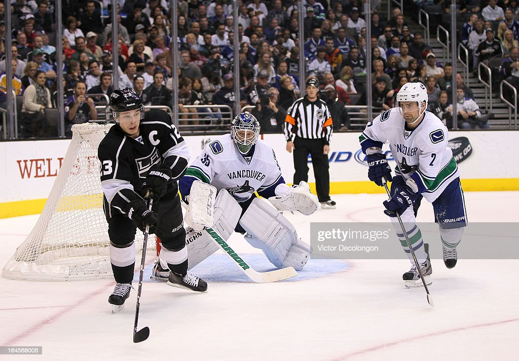 Defenseman Dan Hamhuis #2 and goaltender Cory Schneider #35 of the Vancouver Canucks defend their net from the play of Dustin Brown #23 of the Los Angeles Kings during the NHL game at Staples Center on March 23, 2013 in Los Angeles, California. The Canucks defeated the Kings 1-0.