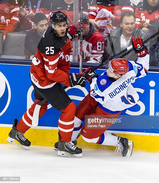 Defenseman Darnell Nurse of Canada places a hit against forward Pavel Buchnevich of Russia during the Gold medal game of the 2015 IIHF World Junior...
