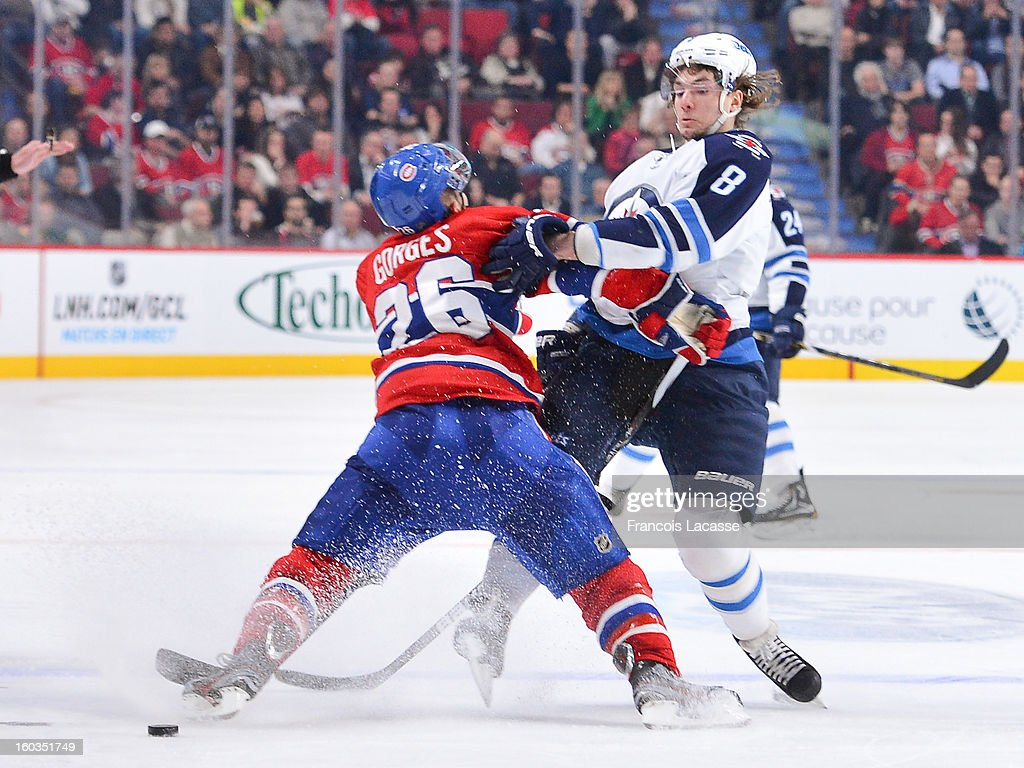 Defenseman Josh Georges #26 of the Montreal Canadiens hits <a gi-track='captionPersonalityLinkClicked' href=/galleries/search?phrase=Alexander+Burmistrov&family=editorial&specificpeople=4782297 ng-click='$event.stopPropagation()'>Alexander Burmistrov</a> #8 of the Winnipeg Jets in NHL action on January 29, 2013 at the Bell Centre in Montreal, Quebec, Canada.