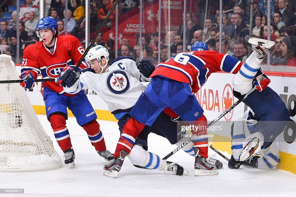 Defenseman Josh Georges #26 of the Montreal Canadiens trips <a gi-track='captionPersonalityLinkClicked' href=/galleries/search?phrase=Andrew+Ladd&family=editorial&specificpeople=228452 ng-click='$event.stopPropagation()'>Andrew Ladd</a> #16 of the Winnipeg Jets as teammate <a gi-track='captionPersonalityLinkClicked' href=/galleries/search?phrase=Raphael+Diaz&family=editorial&specificpeople=5333791 ng-click='$event.stopPropagation()'>Raphael Diaz</a> #61 follows the play in NHL action on January 29, 2013 at the Bell Centre in Montreal, Quebec, Canada.