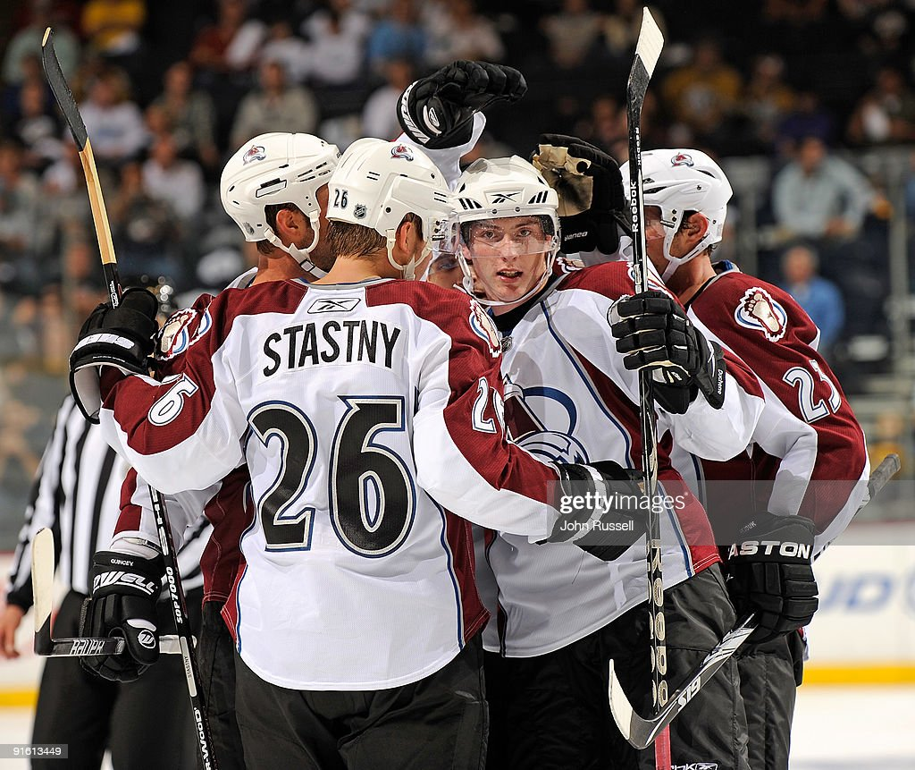 Defenseman Kyle Quincey #27 of the Colorado Avalanche looks at the camera as he is congratulated by teammates center Paul Stastny #26 and right wing Milan Hejduk #23 after scoring a goal against the Nashville Predators on October 8, 2009 at the Sommet Center in Nashville, Tennessee.
