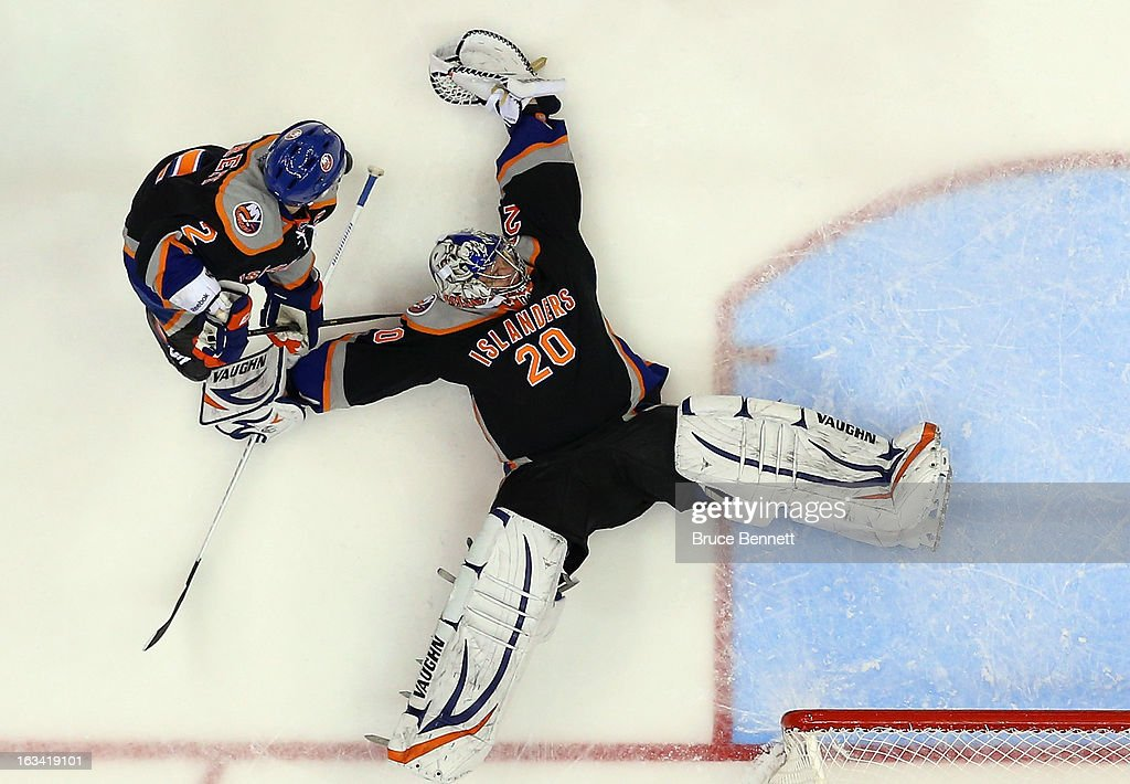 Defenseman <a gi-track='captionPersonalityLinkClicked' href=/galleries/search?phrase=Mark+Streit&family=editorial&specificpeople=636976 ng-click='$event.stopPropagation()'>Mark Streit</a> #2 of the New York Islanders and goaltender <a gi-track='captionPersonalityLinkClicked' href=/galleries/search?phrase=Evgeni+Nabokov&family=editorial&specificpeople=171380 ng-click='$event.stopPropagation()'>Evgeni Nabokov</a> #20 of the New York Islanders defend the net against the Washington Capitals at the Nassau Veterans Memorial Coliseum on March 9, 2013 in Uniondale, New York. The Islanders defeated the Capitals 5-2.
