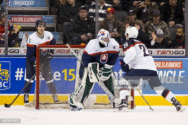 Defenseman Martin Bodak of Team Slovakia holds the puck behind his net while forward Jack Roslovic of Team United States stands in front of...