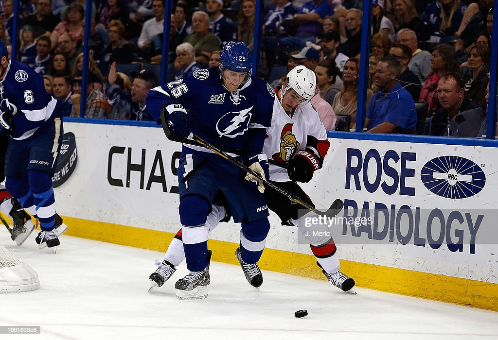Defenseman Matthew Carle #25 of the Tampa Bay Lightning battles center Kyle Turris #7 of the Ottawa Senators for the puck along the boards during the game at the Tampa Bay Times Forum on April 9, 2013 in Tampa, Florida.