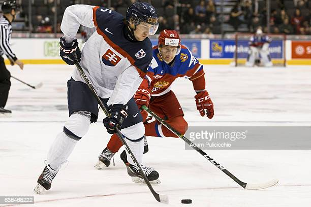 Defenseman Michal Roman of Team Slovakia tries to hold onto the puck as forward Denis Guryanov of Team Russia attacks in a preliminary round Group B...