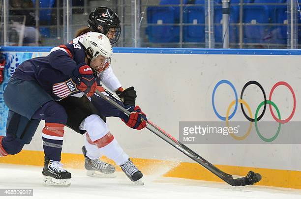 USA defenseman Michelle Picard plays Switzerland forward Jessica Lutz off the puck during the first period in a women's hockey game at the Winter...