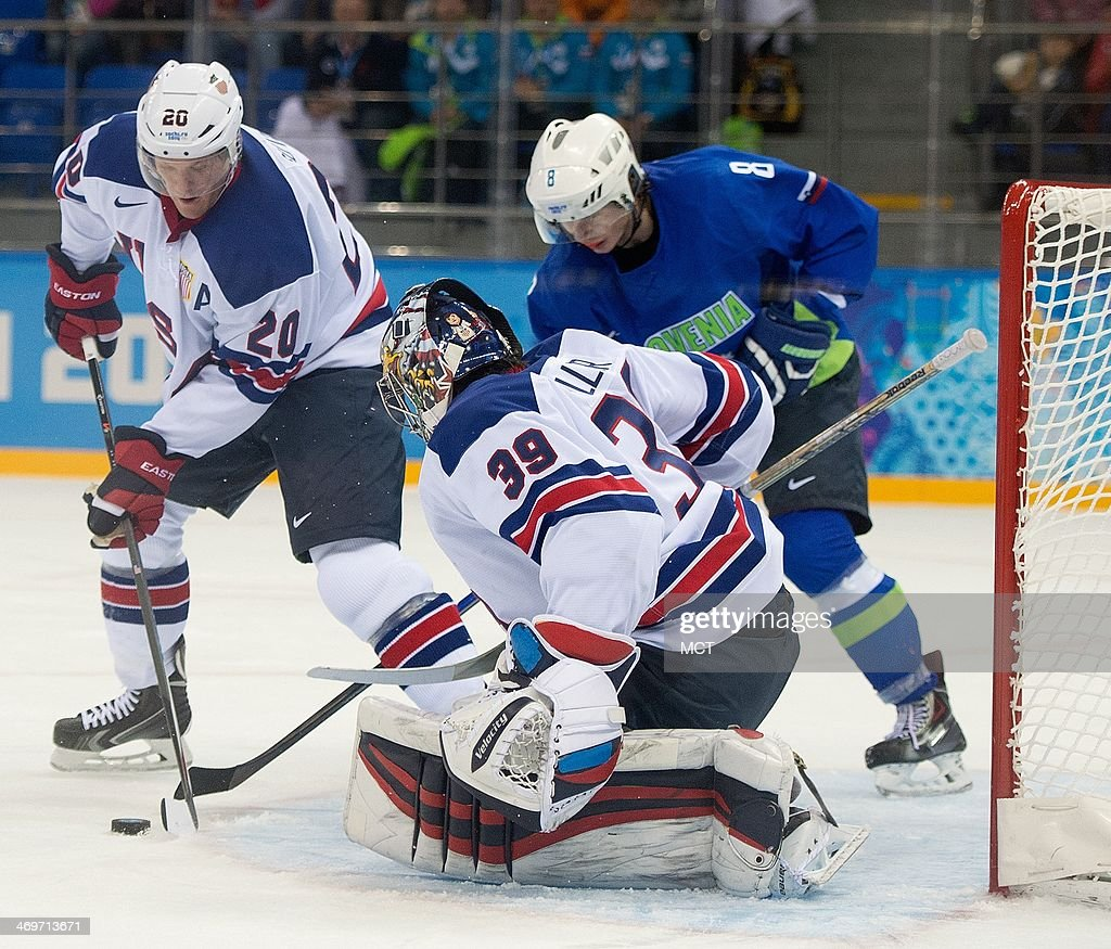 USA defenseman Ryan Suter (20) helps goalie Ryan Miller (39) protect the goal on a shot by Slovenia forward Ziga Jeglic (8) during the third period in a men's hockey game at the Winter Olympics in Sochi, Russia, Sunday, February 16, 2014. USA defeated Slovenia 5-1.