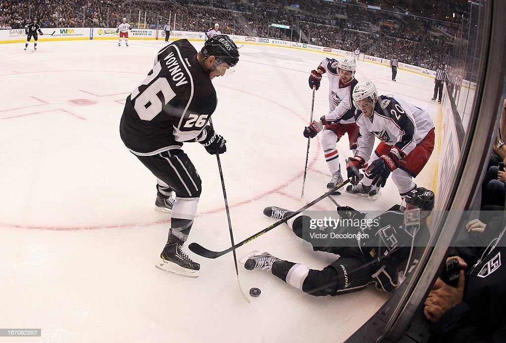 Defenseman <a gi-track='captionPersonalityLinkClicked' href=/galleries/search?phrase=Slava+Voynov&family=editorial&specificpeople=8315719 ng-click='$event.stopPropagation()'>Slava Voynov</a> #26 of the Los Angeles Kings plays the puck from <a gi-track='captionPersonalityLinkClicked' href=/galleries/search?phrase=Nick+Foligno&family=editorial&specificpeople=537821 ng-click='$event.stopPropagation()'>Nick Foligno</a> #71 and <a gi-track='captionPersonalityLinkClicked' href=/galleries/search?phrase=Tim+Erixon+-+Hockey+sur+glace&family=editorial&specificpeople=8546945 ng-click='$event.stopPropagation()'>Tim Erixon</a> #20 of the Columbus Blue Jackets as <a gi-track='captionPersonalityLinkClicked' href=/galleries/search?phrase=Trevor+Lewis&family=editorial&specificpeople=543187 ng-click='$event.stopPropagation()'>Trevor Lewis</a> #22 of the Los Angeles Kings falls to the ice in the third period during the NHL game at Staples Center on April 18, 2013 in Los Angeles, California. The Kings defeated the Blue Jackets 2-1.