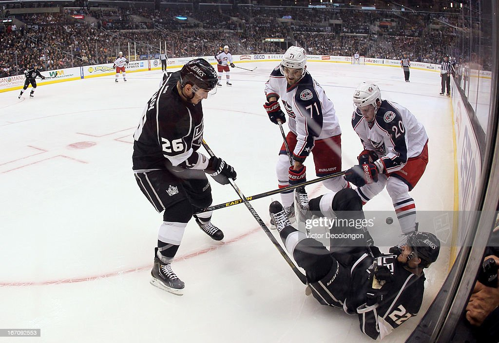 Defenseman <a gi-track='captionPersonalityLinkClicked' href=/galleries/search?phrase=Slava+Voynov&family=editorial&specificpeople=8315719 ng-click='$event.stopPropagation()'>Slava Voynov</a> #26 of the Los Angeles Kings plays the puck from <a gi-track='captionPersonalityLinkClicked' href=/galleries/search?phrase=Nick+Foligno&family=editorial&specificpeople=537821 ng-click='$event.stopPropagation()'>Nick Foligno</a> #71 and <a gi-track='captionPersonalityLinkClicked' href=/galleries/search?phrase=Tim+Erixon+-+Ice+Hockey+Player&family=editorial&specificpeople=8546945 ng-click='$event.stopPropagation()'>Tim Erixon</a> #20 of the Columbus Blue Jackets as <a gi-track='captionPersonalityLinkClicked' href=/galleries/search?phrase=Trevor+Lewis&family=editorial&specificpeople=543187 ng-click='$event.stopPropagation()'>Trevor Lewis</a> #22 of the Los Angeles Kings falls to the ice in the third period during the NHL game at Staples Center on April 18, 2013 in Los Angeles, California. The Kings defeated the Blue Jackets 2-1.