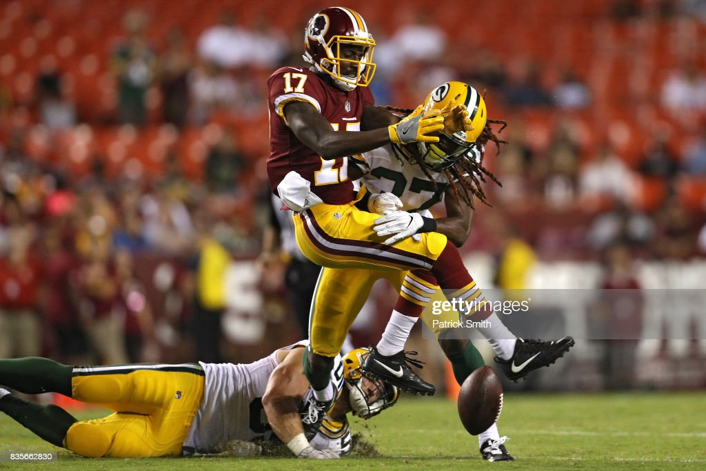Defensive back Aaron Taylor #37 of the Green Bay Packers tackles wide receiver James Quick #17 of the Washington Redskins in the fourth quarter during a preseason game at FedExField on August 19, 2017 in Landover, Maryland.