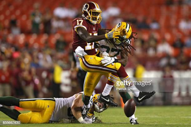 Defensive back Aaron Taylor of the Green Bay Packers tackles wide receiver James Quick of the Washington Redskins in the fourth quarter during a...