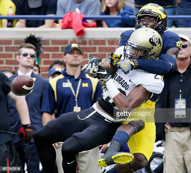 Defensive back Ahkello Witherspoon of the Colorado Buffaloes breaks up a pass intended for wide receiver Amara Darboh of the Michigan Wolverines...
