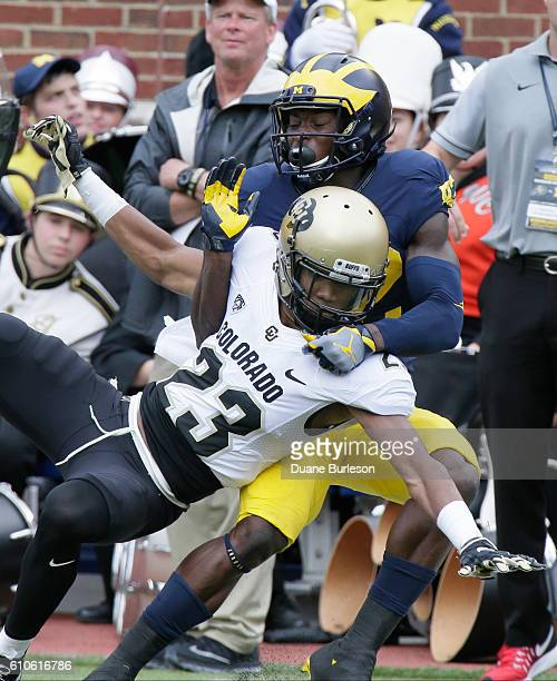 Defensive back Ahkello Witherspoon of the Colorado Buffaloes tangles up with wide receiver Amara Darboh of the Michigan Wolverines after breaking up...