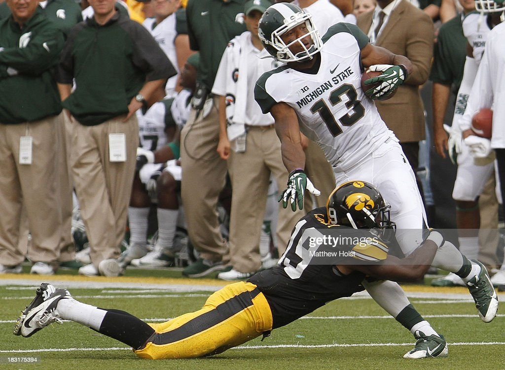 Defensive back B.J. Lowery #19 of the Iowa Hawkeyes makes a tackle during the fourth quarter on wide receiver Bennie Fowler #13 of the Michigan State Spartans on October 5, 2013 at Kinnick Stadium in Iowa City, Iowa. Michigan State won 26-14.