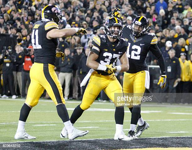Defensive back Brandon Snyder of the Iowa Hawkeyes is congratulated by defensive back Anthony Gair and linebacker Bo Bower after breaking up a play...