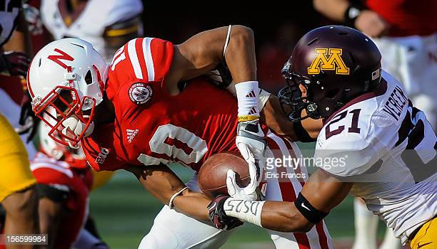 Defensive back Brock Vereen of the Minnesota Golden Gophers tries to strip the ball from wide receiver Jamal Turner of the Nebraska Cornhuskers...