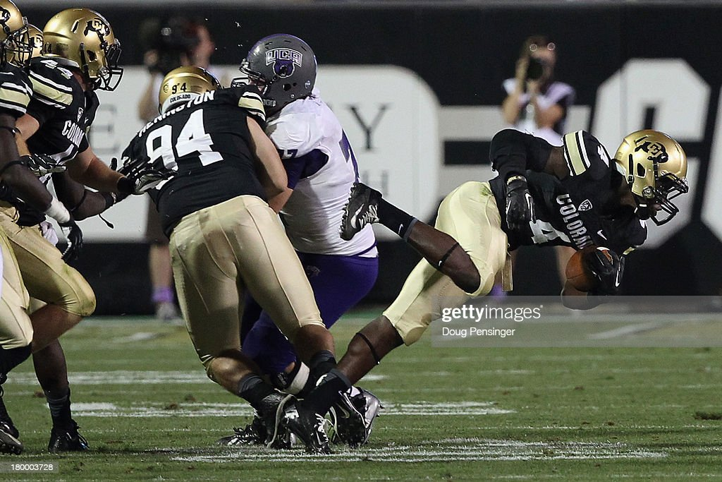 Defensive back Chidobe Awuzie #4 of the Colorado Buffaloes advances the ball after stripping it from wide receiver Jatavious Wilson #14 of the Central Arkansas Bears after a fourth quarter reception at Folsom Field on September 7, 2013 in Boulder, Colorado. The Buffaloes defeated the Bears 38-24.