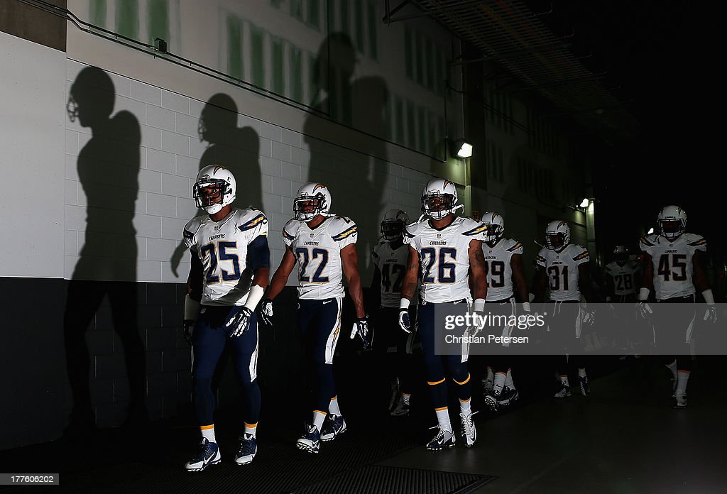 defensive back Darrell Stuckey #25, cornerback Derek Cox #22 and defensive back Johnny Patrick #26 of the San Diego Chargers lead teammates out onto the field before the preseason NFL game against the Arizona Cardinals at the University of Phoenix Stadium on August 24, 2013 in Glendale, Arizona.
