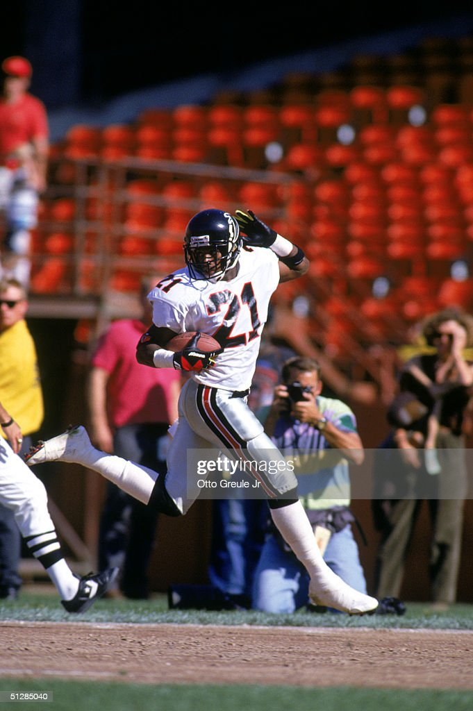 Defensive back Deion Sanders of the Atlanta Falcons looks back over his shoulder as he celebrates running the ball against the San Francisco 49ers...