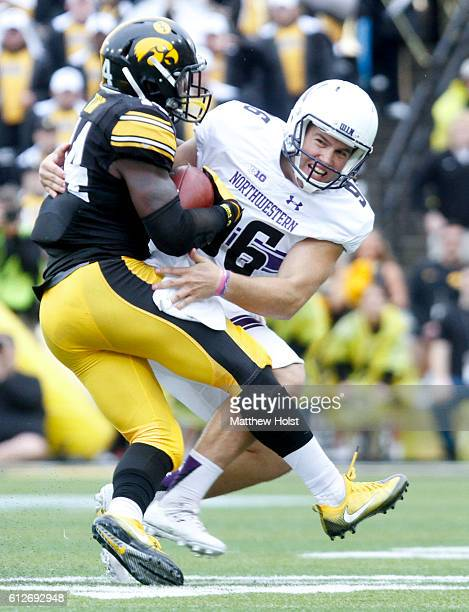 Defensive back Desmond King of the Iowa Hawkeyes is pulled down during the second quarter by punter Hunter Niswander of the Northwestern Wildcats on...