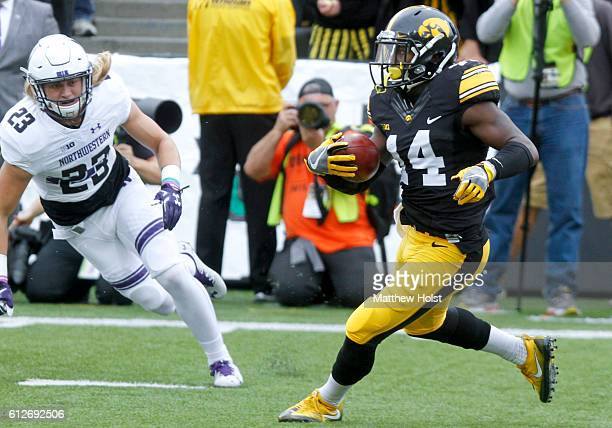 Defensive back Desmond King of the Iowa Hawkeyes runs back a return during the first quarter past wide receiver Steven Reese of the Northwestern...