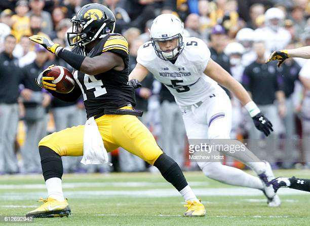 Defensive back Desmond King of the Iowa Hawkeyes runs back a return during the second quarter in front of wide receiver Charlie Fessler of the...