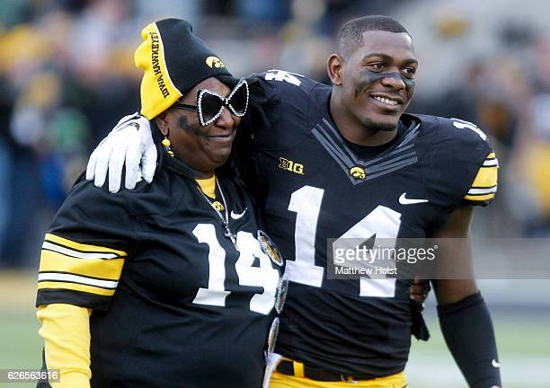 Defensive back Desmond King of the Iowa Hawkeyes walks with his mom Yvette Powell after being announced on senior day before the matchup against the...