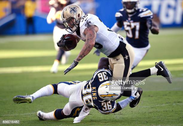 Defensive back Desmond King of the Los Angeles Chargers tackles running back Daniel Lasco of the New Orleans Saints short of the first down during...