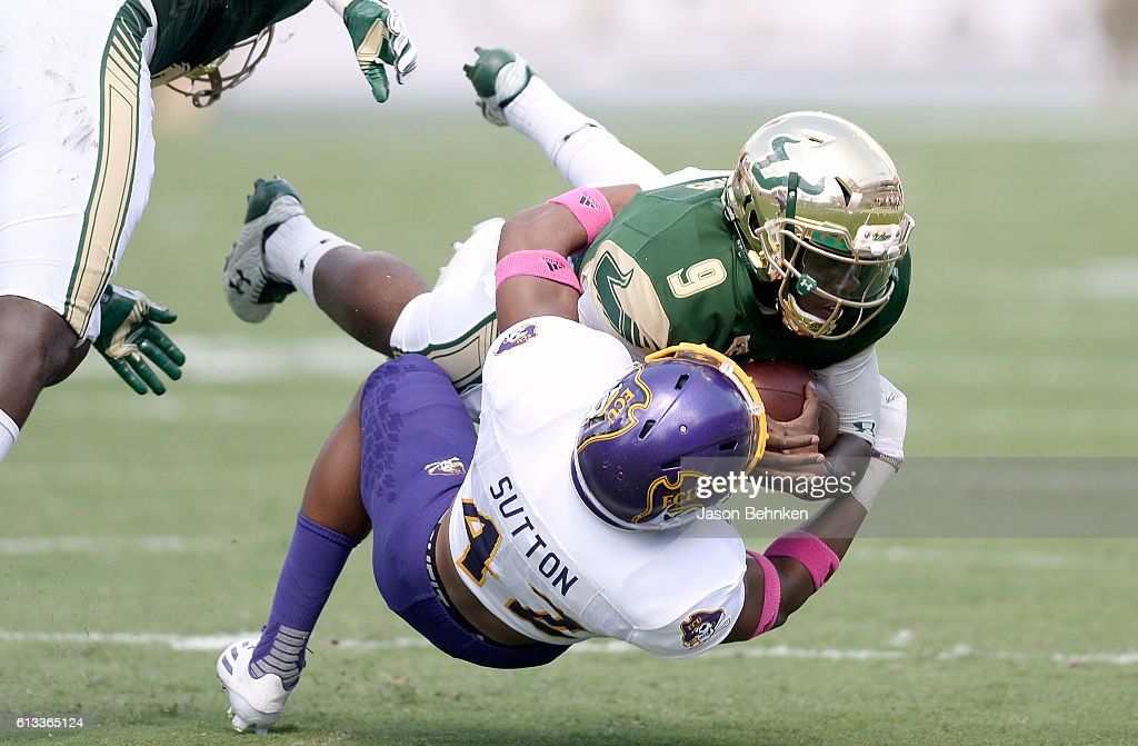 Defensive back Devon Sutton of the East Carolina Pirates tackles quarterback Quinton Flowers of the South Florida Bulls during the 1st quarter at...