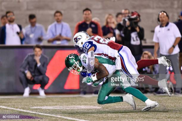 Defensive back Greg Henderson of the Montreal Alouettes jumps on top of wide receiver Caleb Holley of the Saskatchewan Roughriders in the second half...