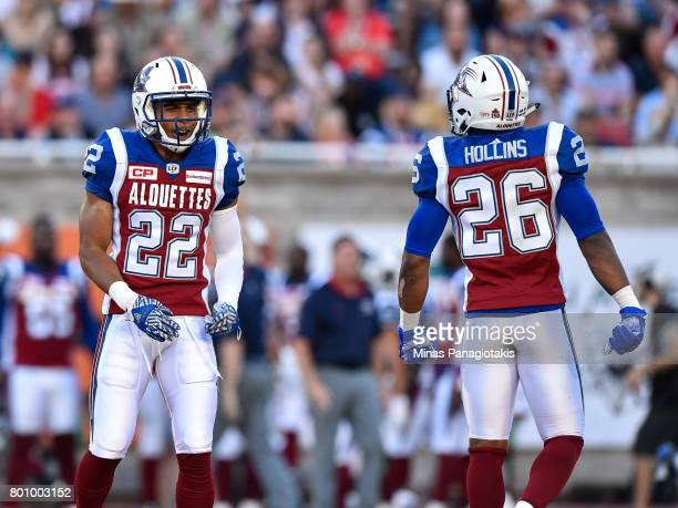 Defensive back Greg Henderson speaks with defensive back Tyree Hollins of the Montreal Alouettes against the Saskatchewan Roughriders during the CFL...