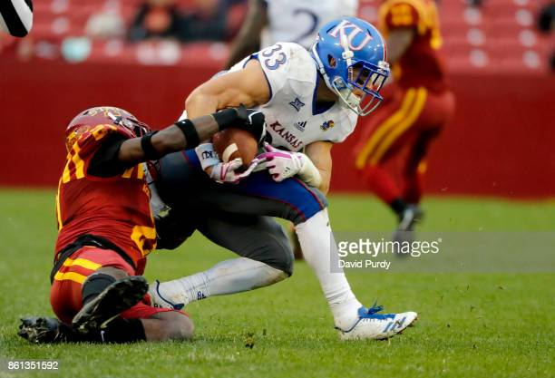 Defensive back Jatairis Grant of the Iowa State Cyclones tackles wide receiver Ryan Schadler of the Kansas Jayhawks as he rushed for yards in the...
