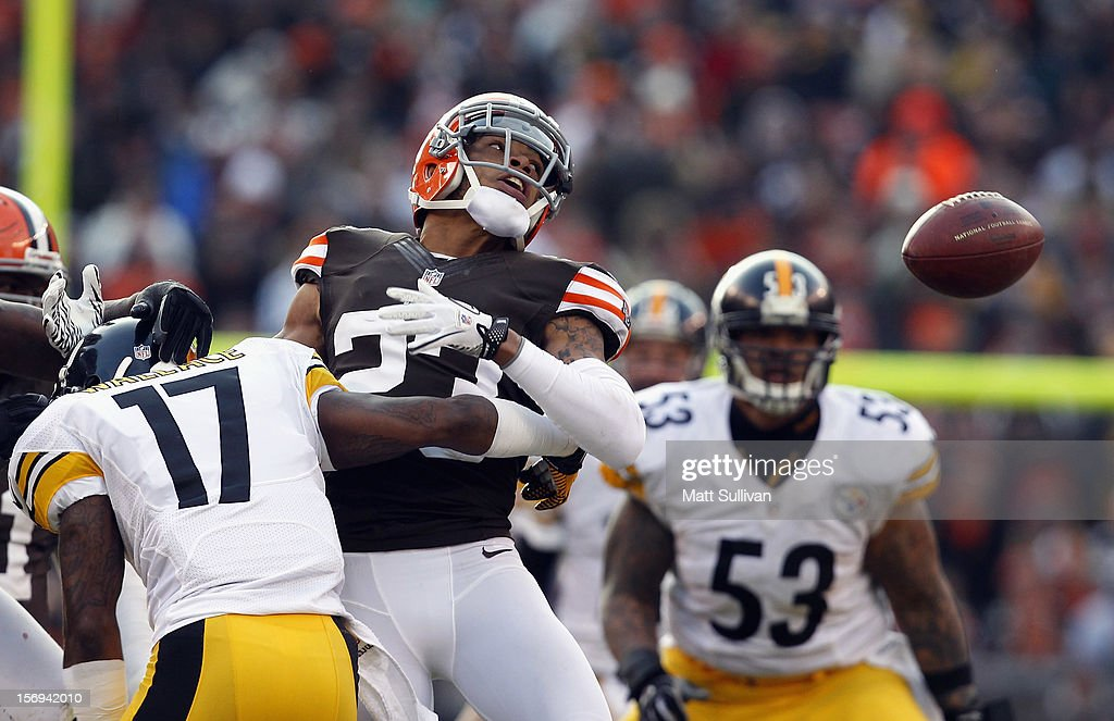 Defensive back Joe Haden #23 of the Cleveland Browns looks at a ball intercepted by defensive lineman Billy Winn #90 as he is hit by wide receiver Mike Wallace #17 of the Pittsburgh Steelers at Cleveland Browns Stadium on November 25, 2012 in Cleveland, Ohio.