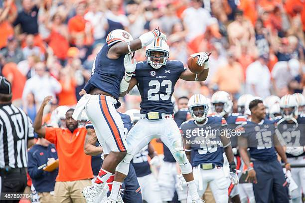 Defensive back Johnathan Ford of the Auburn Tigers celebrates with linebacker Jeff Holland of the Auburn Tigers after intercepting a pass during...